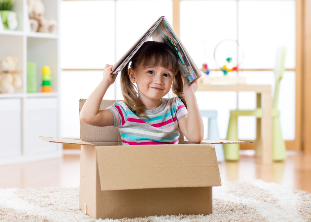Smart,Kid,Girl,Sitting,In,Cardboard,Box,And,Holding,A