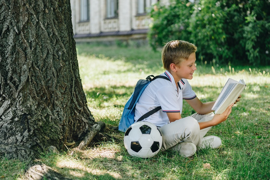 Cute,Smiling,Schoolboy,Reading,Book,While,Sitting,On,Lawn,Near