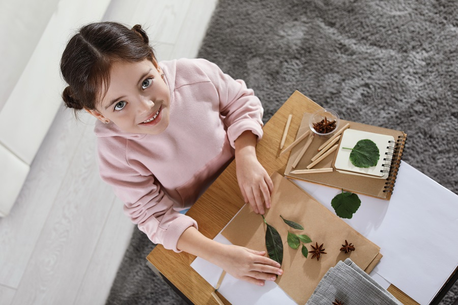 Little,Girl,Working,With,Natural,Materials,At,Table,Indoors,,Top